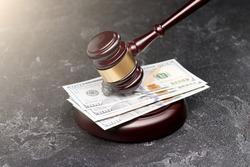 Judge's hammer, banknotes on black background