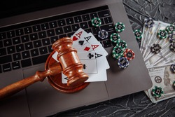 Judge's wooden gavel, poker chips and playing cards. Concept of Law and regulation of gambling