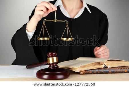 Judge sitting at table during court hearings on grey background - stock photo