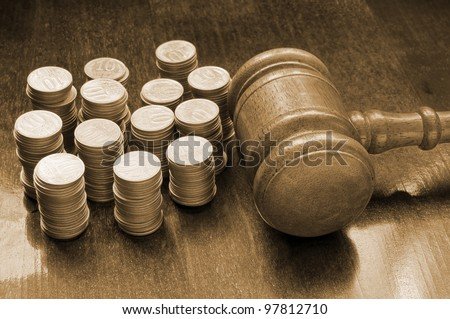 Judges gavel and coins on wooden table