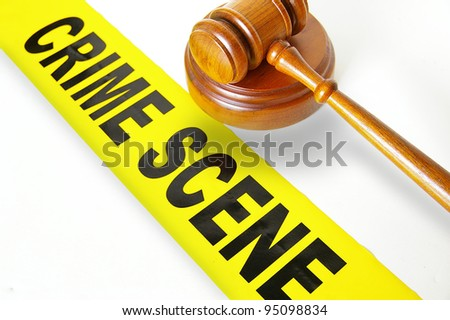 judges gavel and yellow crime scene tape