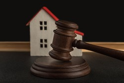 Judges hammer on background of model house. Settle house dealing lawsuit. Confiscated housing. concept of resolving property disputes