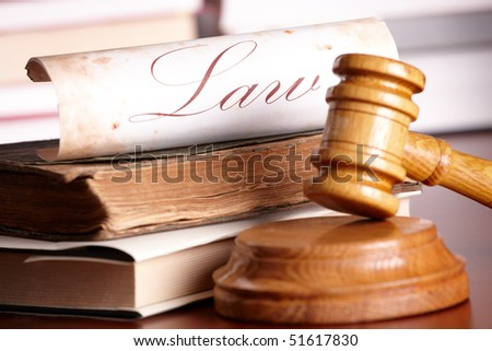 Judges wooden gavel with very old books and paper with word law