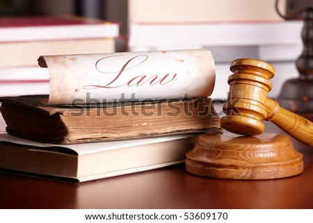 Judges wooden gavel with very old books and paper with word law in the background.