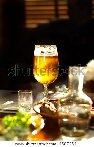 Jug and glass with beer in an interior