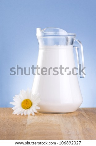 Jug fresh milk and one chamomile flowers is wooden table on a blue background