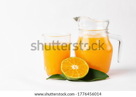 Jug, glass of orange juice and orange fruits with green leaves  on white background