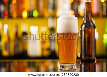 Jug of beer with bottle, placed on bar counter with copy space