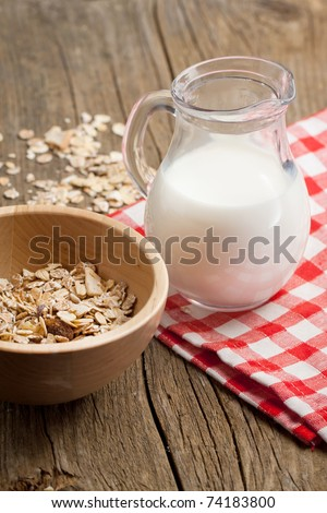 Jug of milk and bowl of dry muesli on old wooden desk