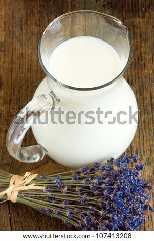 Jug of milk and bunch of lavender flowers on old wooden table