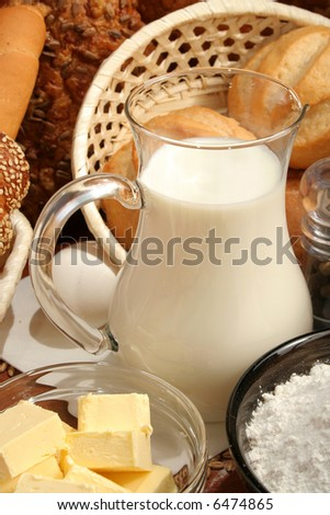 Jug of milk, butter and flour, background