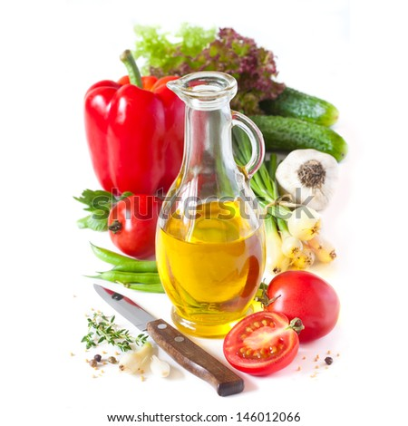 Jug of olive oil and fresh vegetables and spices on a white. - stock photo
