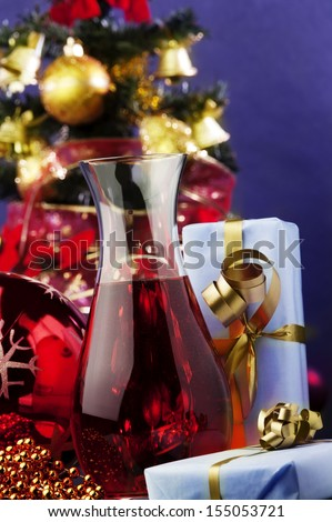 jug of rose wine and Christmas decoration against color background