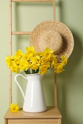 Jug with beautiful daffodils and wicker hat on wooden chair near light green wall
