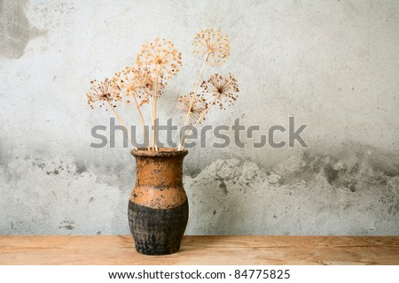 jug with dry flower on a wooden table