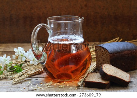 Jug with kvass and rye bread on a wooden table