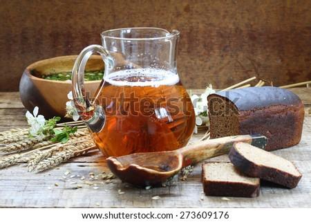 Jug with kvass, okroshka and rye bread on a wooden table