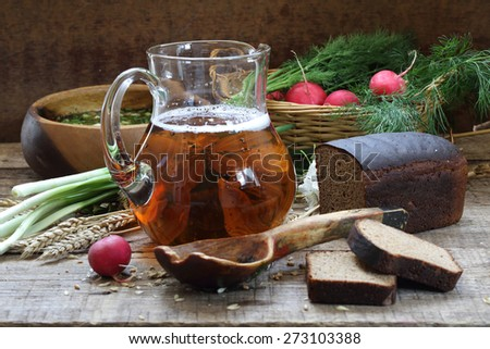 Jug with kvass, rye bread and okroshka in a wooden bowl