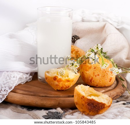 Jug with milk, bread and wild flowers on a white background