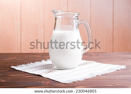 jug with milk on a light wooden table side view