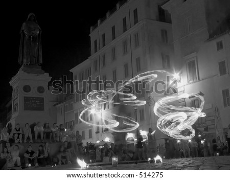 Jugglers with fire, in the square of flowers  in rome italy with the statue of Giordano Bruno (a philosopher who was set on fire in this square by the catholic church for his thoughts)