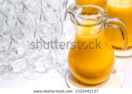 Jugs with freshly squeezed orange juice and clean transparent glasses #1322442137