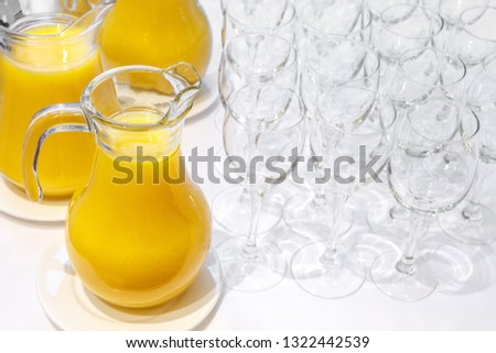 Jugs with freshly squeezed orange juice and clean transparent glasses #1322442539