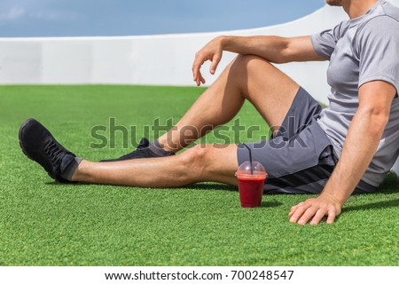 Juice smoothie sport man relaxing enjoying post workout morning breakfast sitting on outdoor grass at home or fitness gym. Athlete drinking red fruit smoothie drink. #700248547