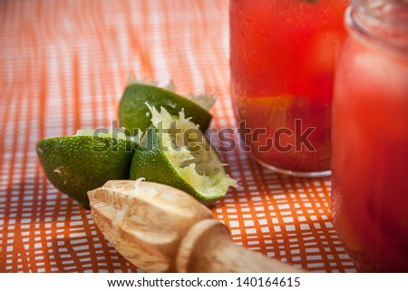 Juiced Limes with a wooden juicer sitting next to margaritas on an orange striped table cloth