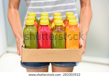 Juicing cold pressed vegetable juices for a detox diet. Dieting by cleansing your body from toxins with raw organic fruits and vegetables juice made fresh and delivered in bottles. #283303922
