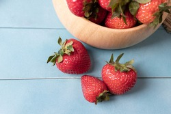 Juicy and fresh organic strawberries in a bowl and some part on a blue wood background.aConcept for healthy nutrition.Close up view.Copy space.