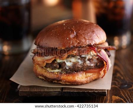 juicy bacon cheeseburger on rustic table