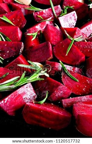 Juicy beet slices before baking. Fresh rosemary. Roast beetroot. Preparation of baked beets. Quarter beets.