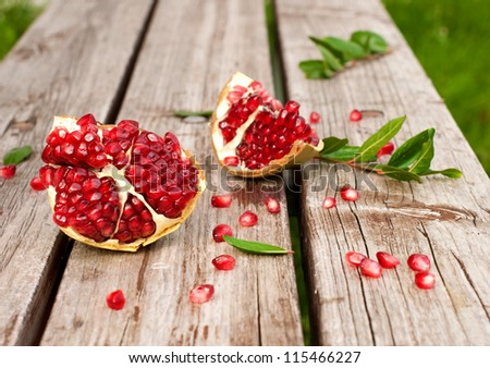 Juicy broken pomegranate with leaves and seeds on a wooden table