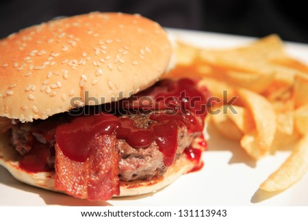 Juicy burger with bacon and fries on a white plate