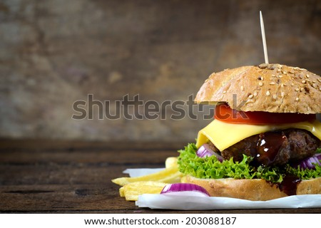 Juicy cheeseburger on the wooden background