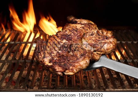 Juicy Chicken Meat Roasted on BBQ Grill. Whole Chicken Grilled On Hot Barbecue Charcoal Flaming Grill.  Backyard Grill Party Dish From Poultry Isolated On Black Background, Closeup View.