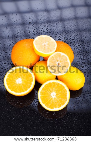 Juicy delicious oranges and lemons on reflective table with water drops