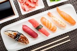 Juicy fresh nigiri sushi dish over the top look. On the plate is sake, tuna, ebi, surimi, unagi, alaska. With ginger slices, soy sauce and wasabi in the background. As well as chopsticks beside