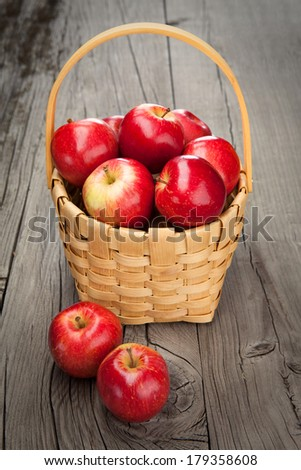 Juicy fresh red apples in basket on dark wooden background