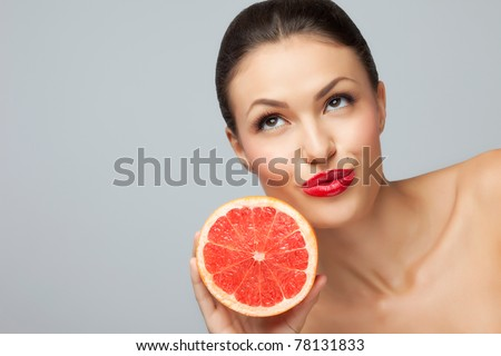 Juicy fruit! A close-up of a pretty lady's face with a fresh luscious grapefruit.