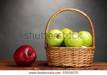 juicy green apples in basket and red apple on wooden table on gray background