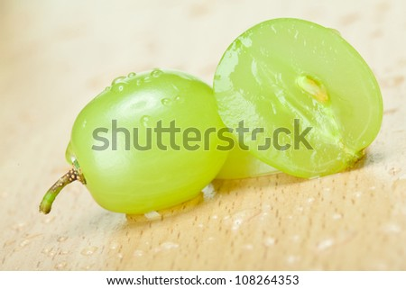 Juicy green grapes - macro shot of whole and cut berries on wooden background - stock photo