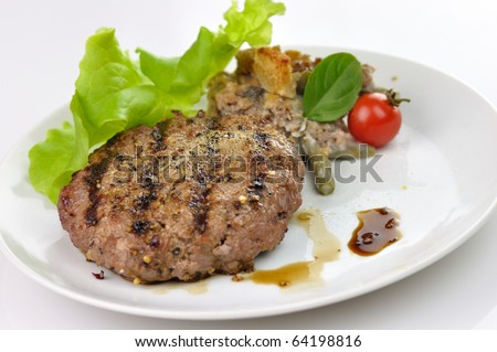 Juicy grilled hamburger with salad and green beans