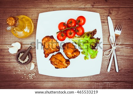 Juicy grilled pork served with cherry tomatoes and lettuce on white plate, white pepper, garlic cloves, bottle of olive oil, knife, fork. Background: wooden boards. Warm toned. Top view. Horizontal.