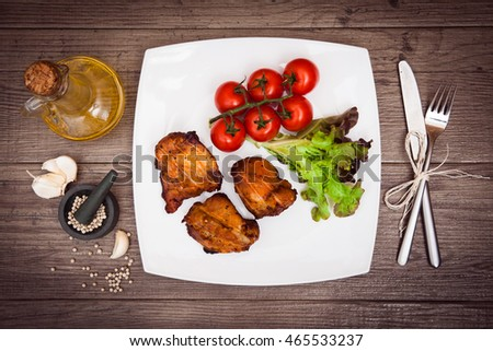 Juicy grilled pork served with cherry tomatoes and lettuce on white plate, white pepper, garlic cloves, bottle of olive oil, knife, fork. Background: wooden boards. Top view. Horizontal.