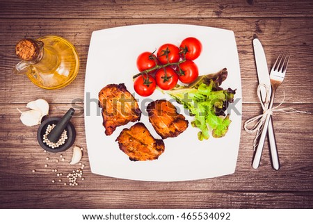 Juicy grilled pork served with cherry tomatoes and lettuce on white plate, white pepper, garlic cloves, bottle of olive oil, knife, fork. Background: wooden boards. Sepia toned. Top view. Horizontal.