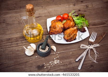 Juicy grilled pork served with cherry tomatoes branch and lettuce on white plate, white pepper, garlic cloves, bottle of olive oil, knife, fork. Background: wooden boards. Top view. Horizontal.