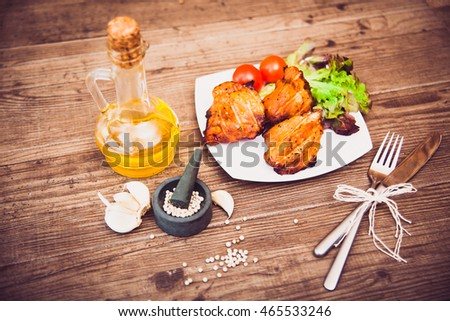 Juicy grilled pork served with cherry tomatoes branch and lettuce on white plate, white pepper, garlic cloves, bottle of olive oil. Sepia toned. Background: wooden boards. Top view. Horizontal.
