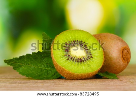 Juicy kiwi fruit on wooden table on green background - stock photo